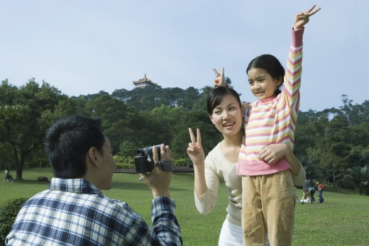 Stock Photo: 1569R-9023448 Man videotaping daughter and wife in park