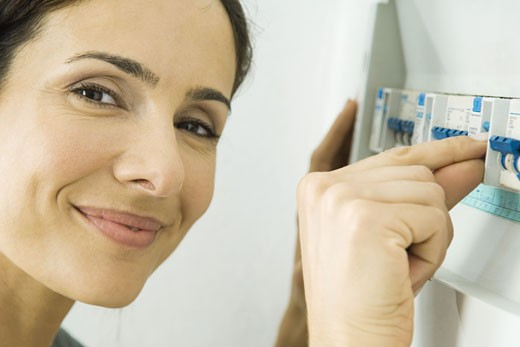 Stock Photo: 1569R-9023626 Woman pushing up lever in fuse box, smiling at camera