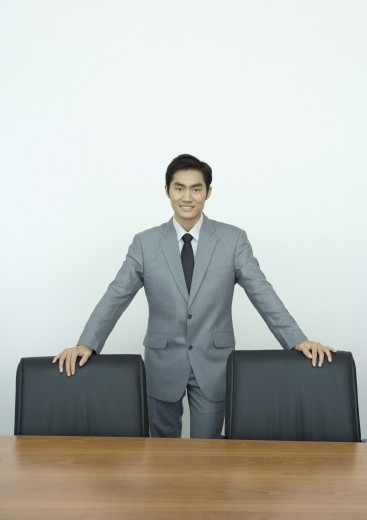 Stock Photo: 1569R-9023681 Businessman standing in conference room with hands on backs of chairs, portrait