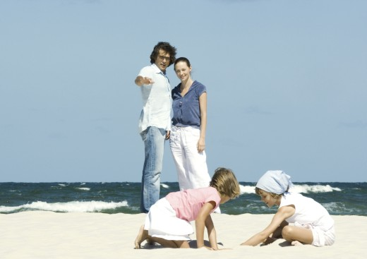 Family on beach, parents watching daughters play in sand : Stock Photo