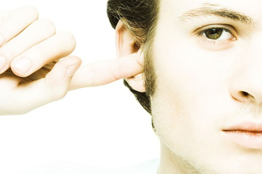 Stock Photo: 1569R-9023929 Young man plugging ear with finger