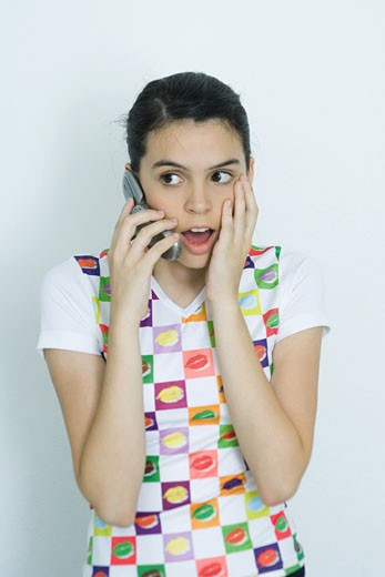 Teenage girl using cell phone, making surprised face, portrait : Stock Photo