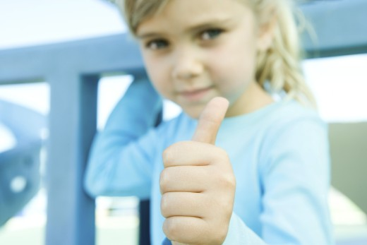 Stock Photo: 1569R-9024255 Girl giving camera thumbs up sign, focus on hand in foreground