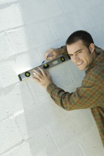 Man drawing line on wall with level : Stock Photo