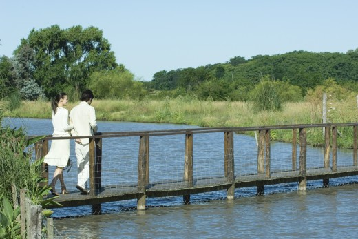 Couple walking over river on footbridge : Stock Photo