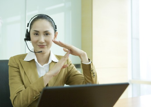 Businesswoman wearing headset and using laptop, making time out gesture : Stock Photo