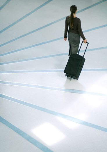 Stock Photo: 1569R-9024409 Woman walking with suitcase, high angle rear view