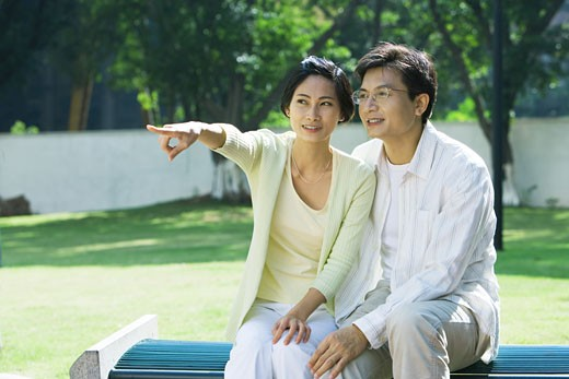 Couple sitting on bench, woman pointing out of frame : Stock Photo