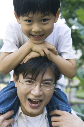 Stock Photo: 1569R-9024427 Boy riding on father's shoulders, front view, smiling at camera