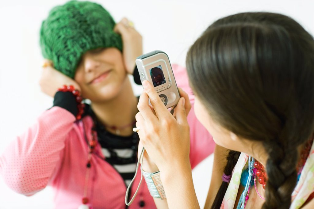 Stock Photo: 1569R-9024826 Two young female friends, one taking photo of the other