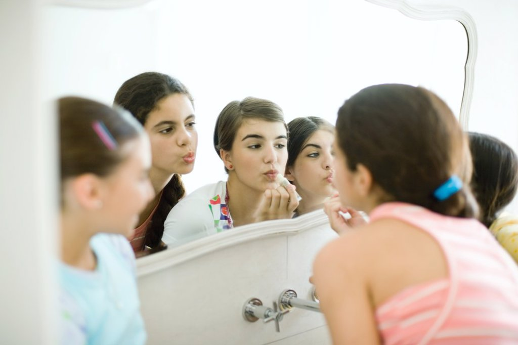 Young female friends looking at mirror, putting on make-up : Stock Photo