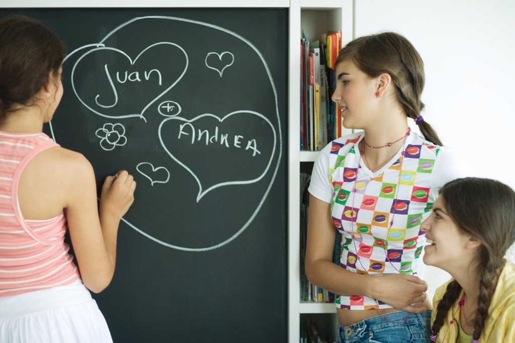 Young female friends writing names in hearts on chalkboard : Stock Photo