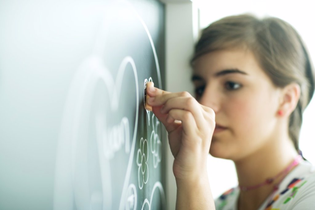 Teen girl drawing on chalkboard : Stock Photo