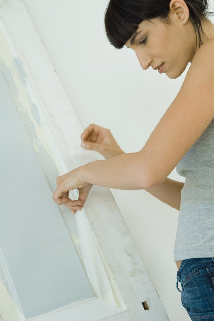 Woman removing masking tape from freshly painted woodwork on door : Stock Photo