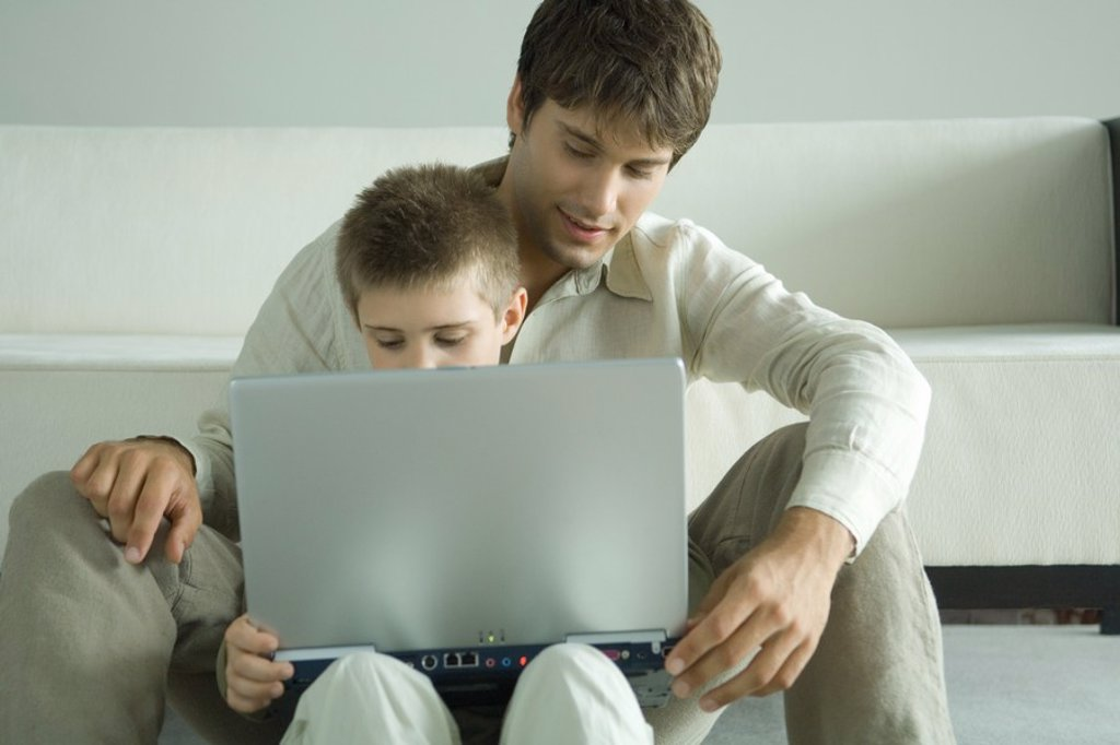 Boy and father using laptop together : Stock Photo