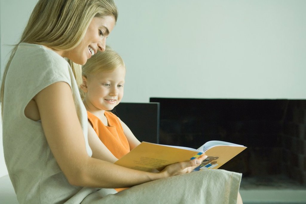 Woman reading book with little girl : Stock Photo
