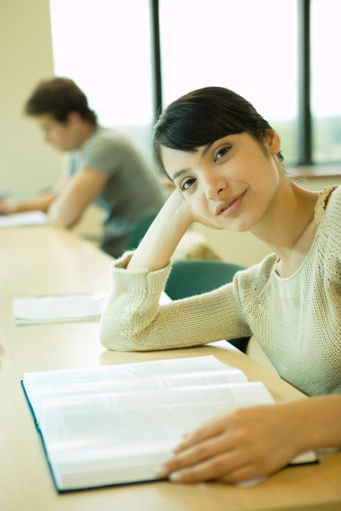 Stock Photo: 1569R-9025314 Young woman studying in university library