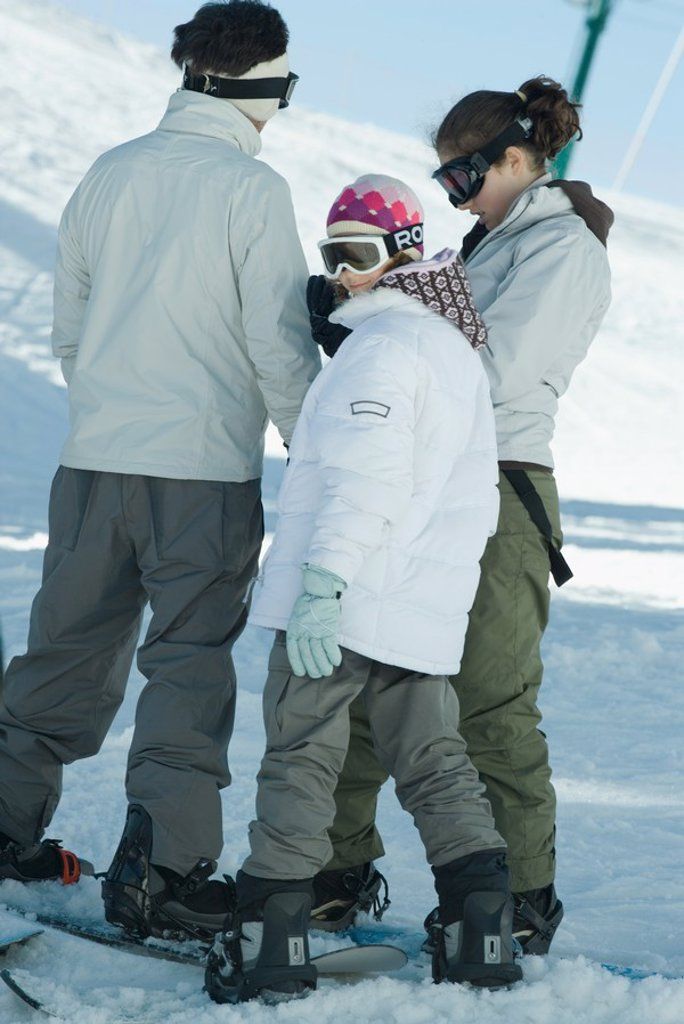 Stock Photo: 1569R-9025408 Snowboarders standing in snow, candid shot, full length