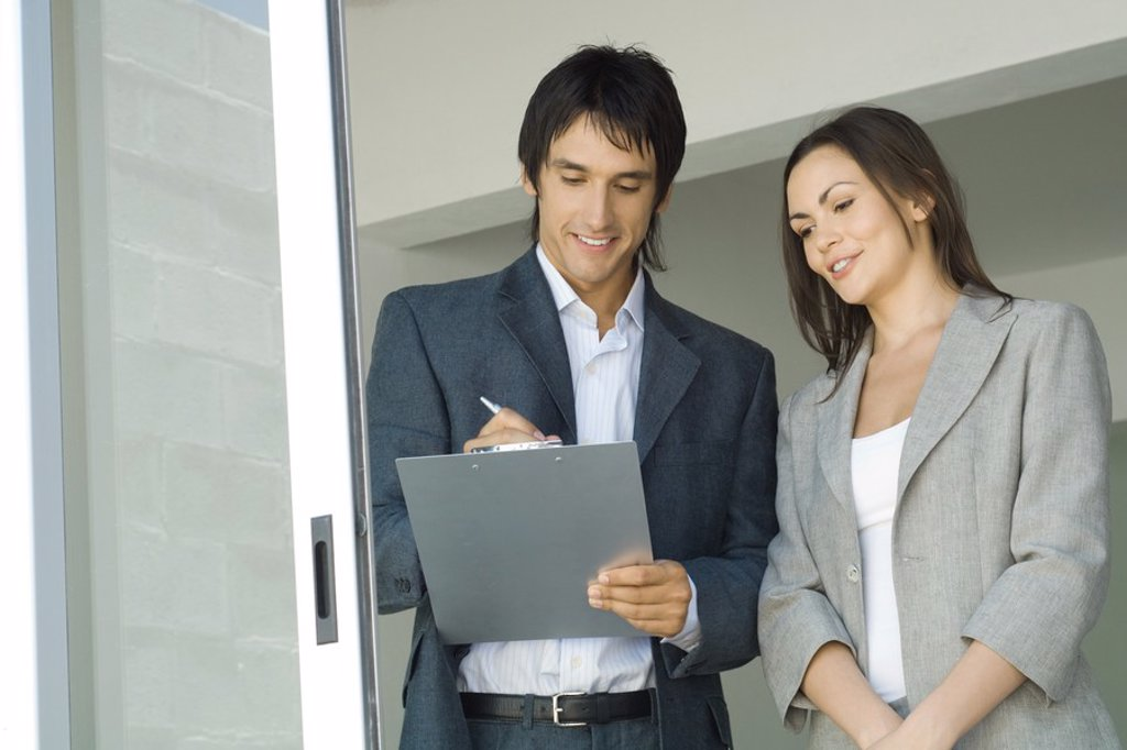 Stock Photo: 1569R-9025444 Male real estate agent showing house to female client, writing on clipboard