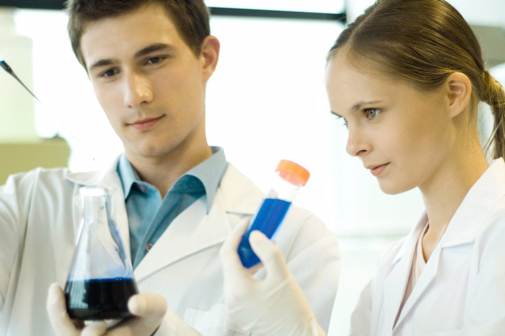 Young male and female scientists holding test tube and flask : Stock Photo