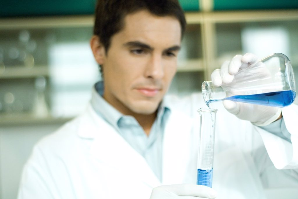 Stock Photo: 1569R-9025554 Male lab worker transferring solution from flask to graduated cylinder