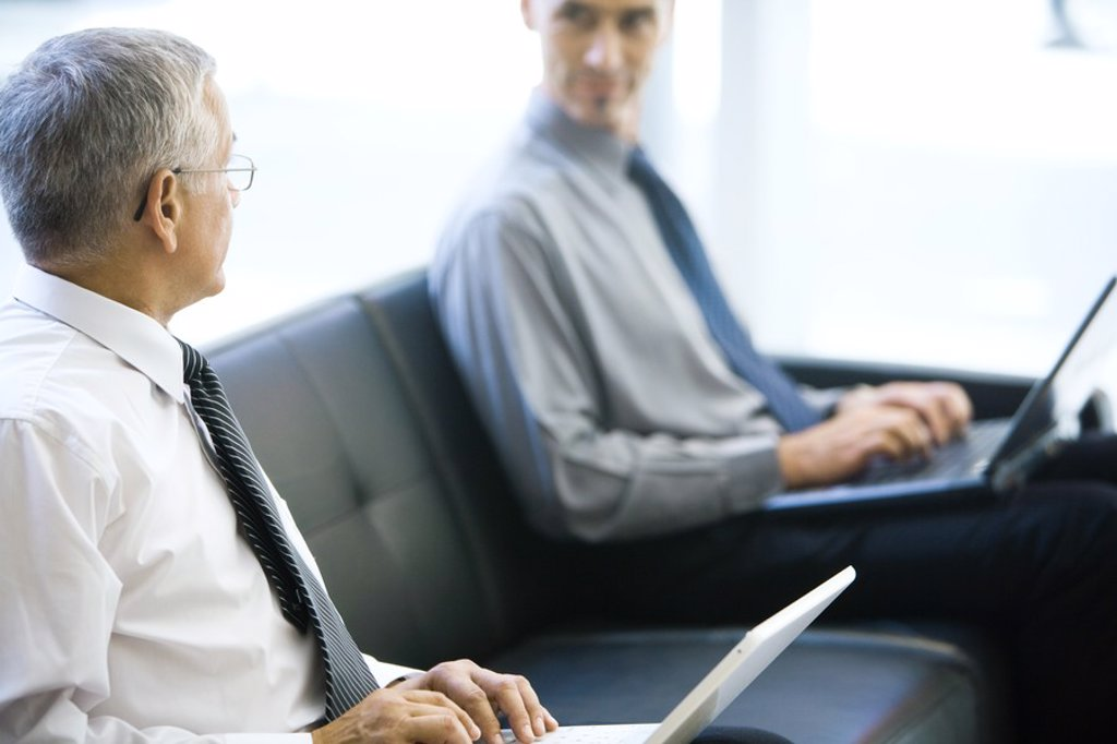 Two businessmen sitting on sofa, looking at each other, both using laptops computers : Stock Photo
