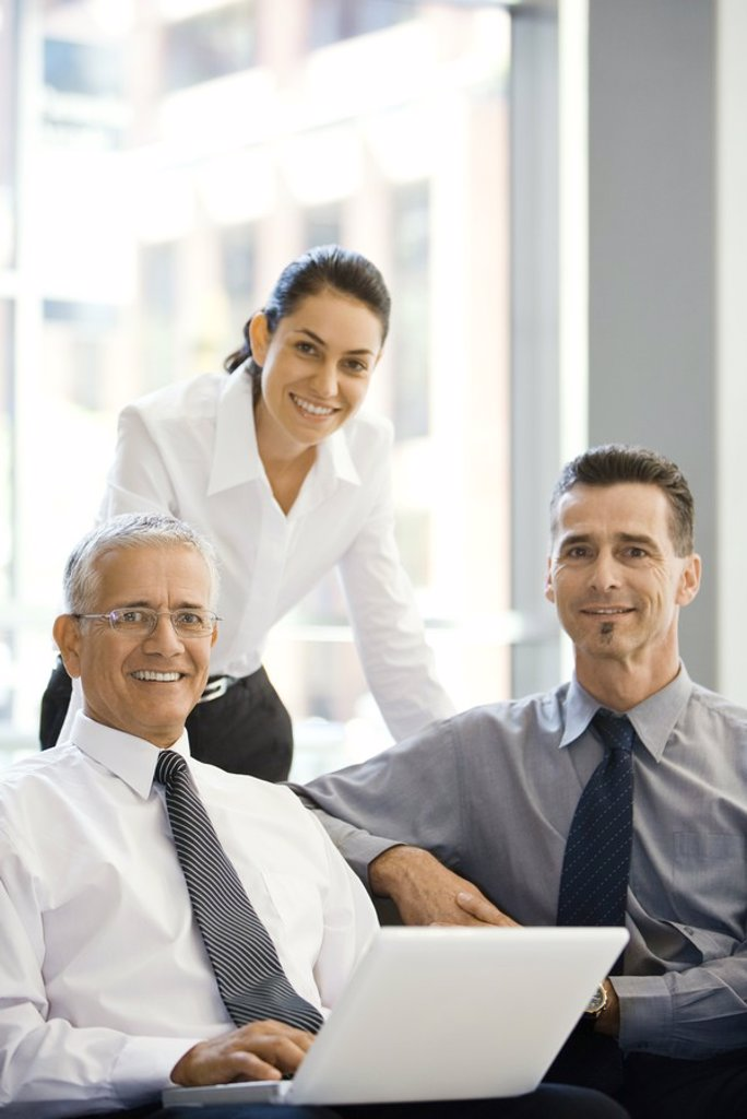 Three business associates smiling at camera, group portrait, one using laptop computer : Stock Photo