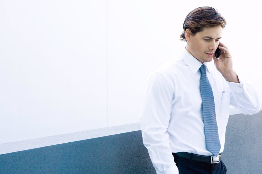 Stock Photo: 1569R-9025727 Young businessman using cell phone, waist up