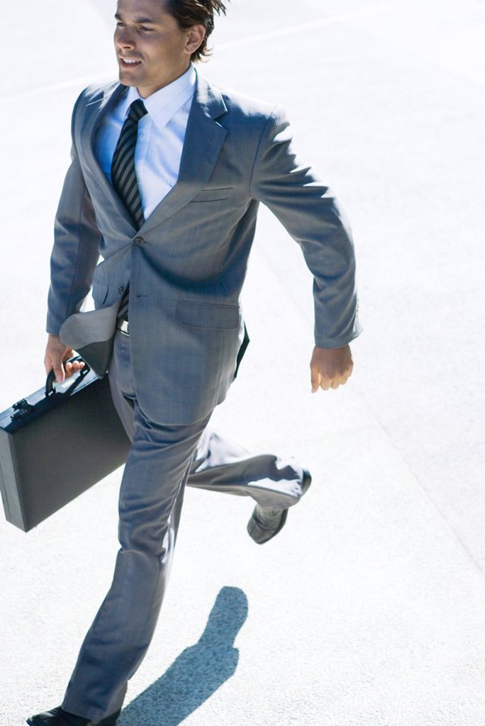 Young businessman running outdoors, carrying briefcase : Stock Photo