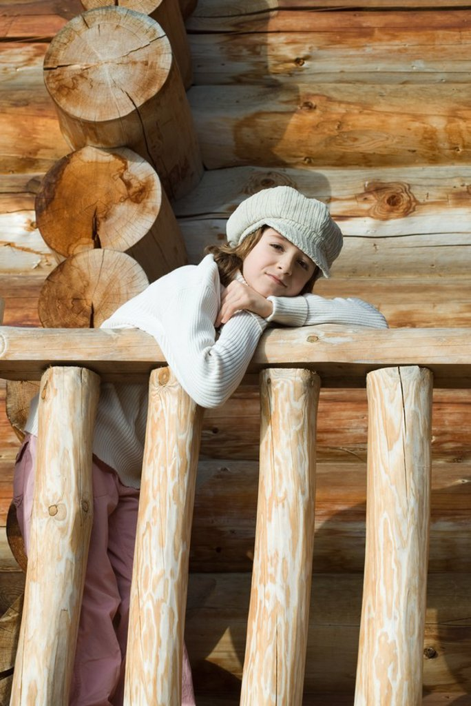 Stock Photo: 1569R-9025929 Girl leaning on railing of log cabin, looking at camera