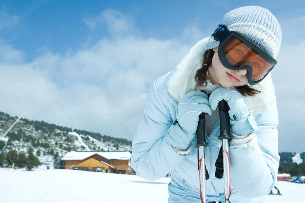 Teen girl leaning on ski sticks, in snowy landscape, portrait : Stock Photo