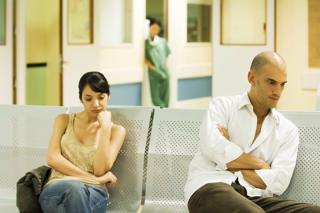 Adults sitting in hospital waiting room, looking away : Stock Photo