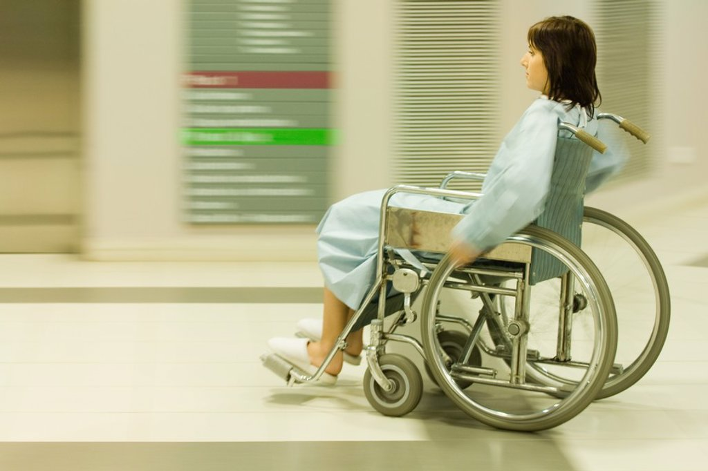 Female patient using wheelchair in hospital corridor, blurred motion : Stock Photo