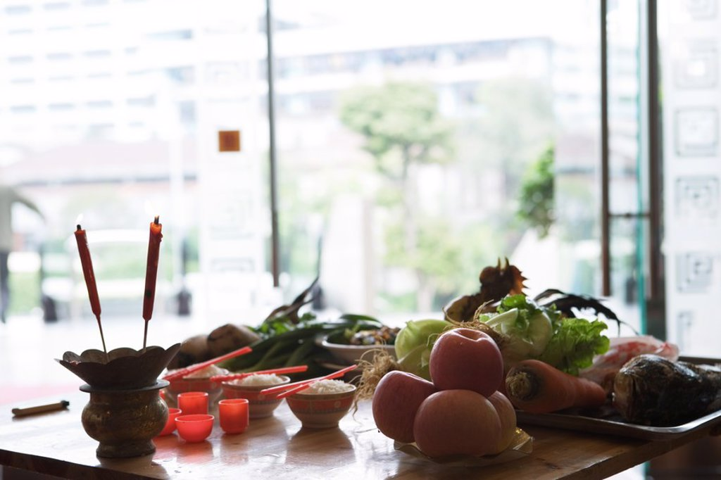 Food and candles on table as religious offering : Stock Photo