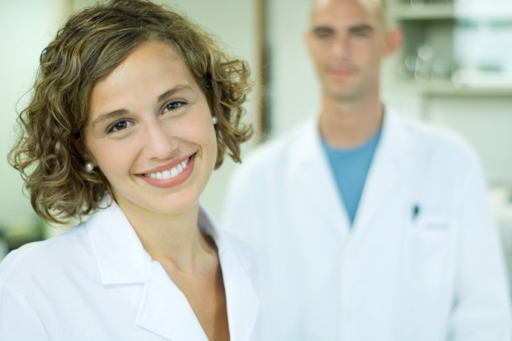 Stock Photo: 1569R-9026356 Female doctor smiling, male colleague in background, portrait