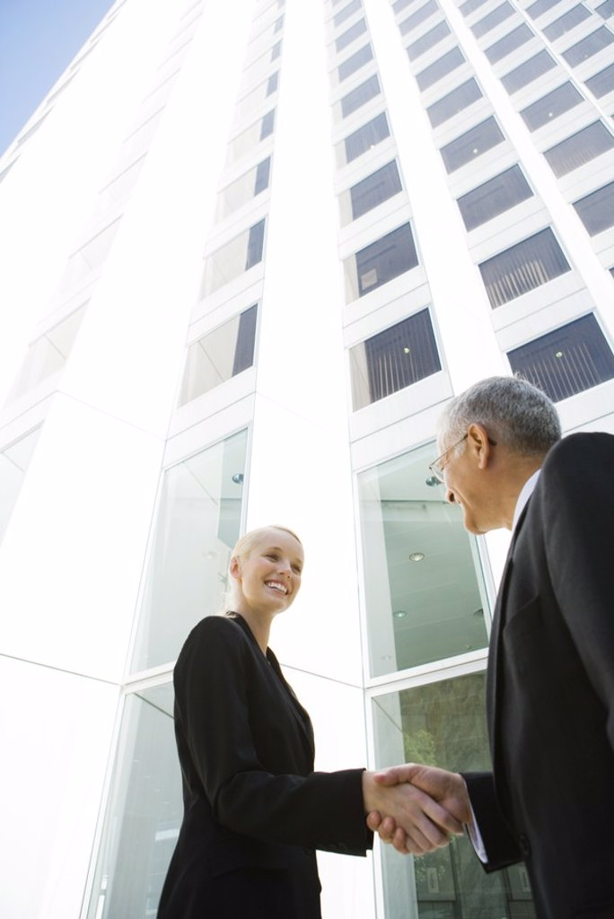 Young businesswoman shaking hands with mature businessman, low angle view : Stock Photo