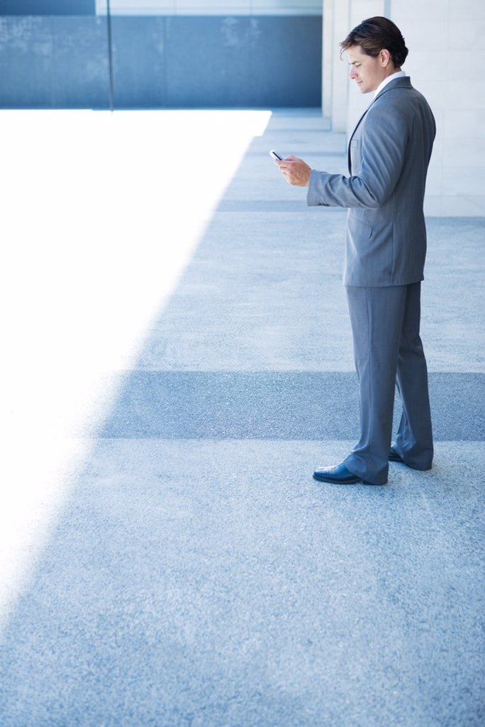 Stock Photo: 1569R-9026511 Businessman looking down at cell phone, full length