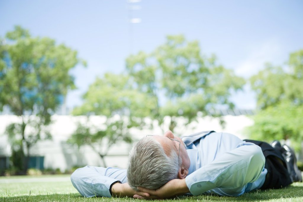 Businessman lying on grass, hands behind head : Stock Photo