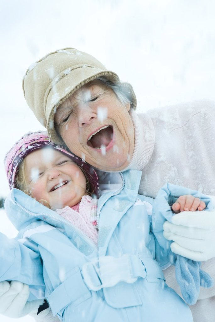 Senior woman and granddaughter cheek to cheek in snow, smiling, eyes, closed : Stock Photo