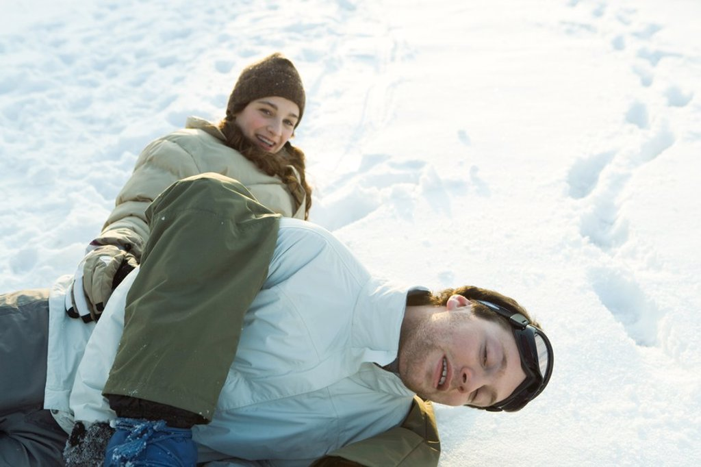 Brother and sister play-fighting in snow, lying in the ground, smiling at camera : Stock Photo