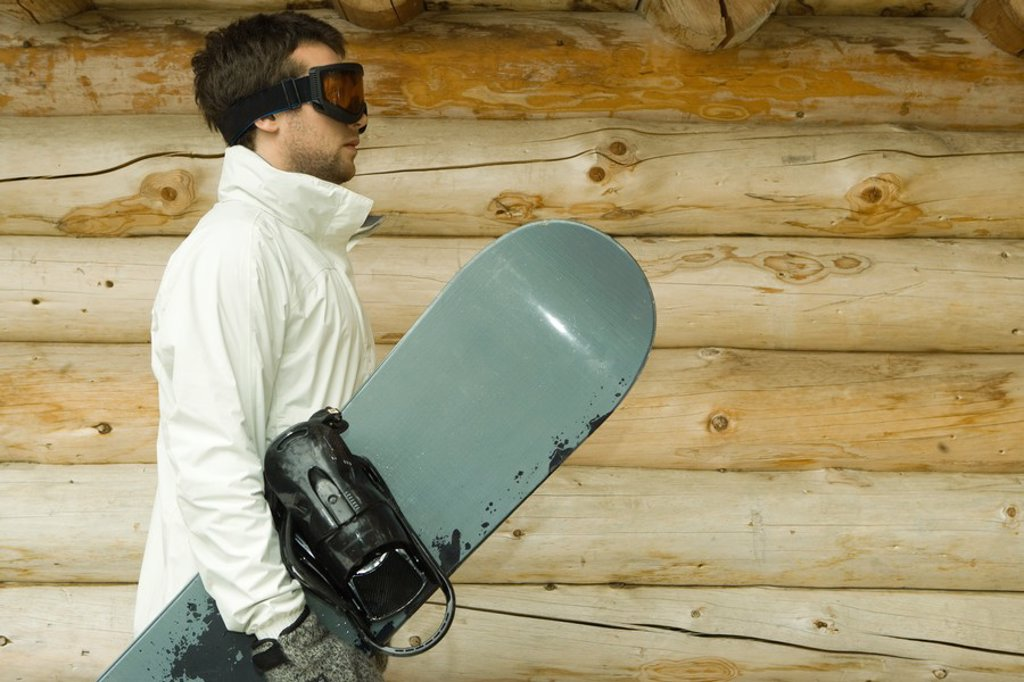 Stock Photo: 1569R-9026663 Young man holding snowboard, side view