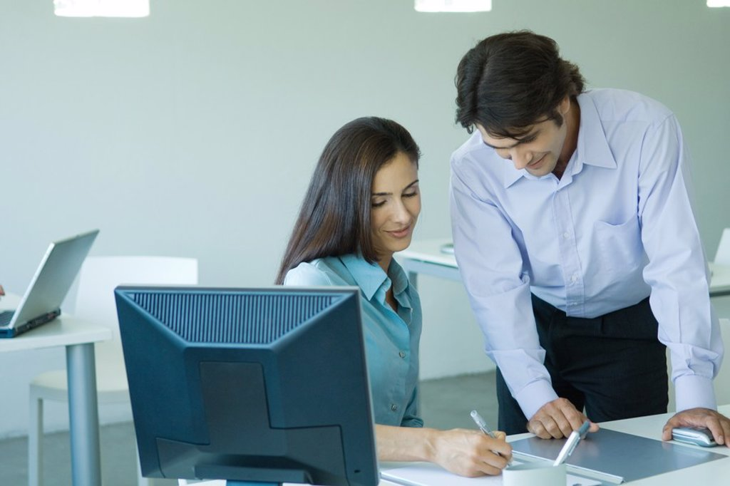 Businesswoman and businessman in office, smiling, writing : Stock Photo