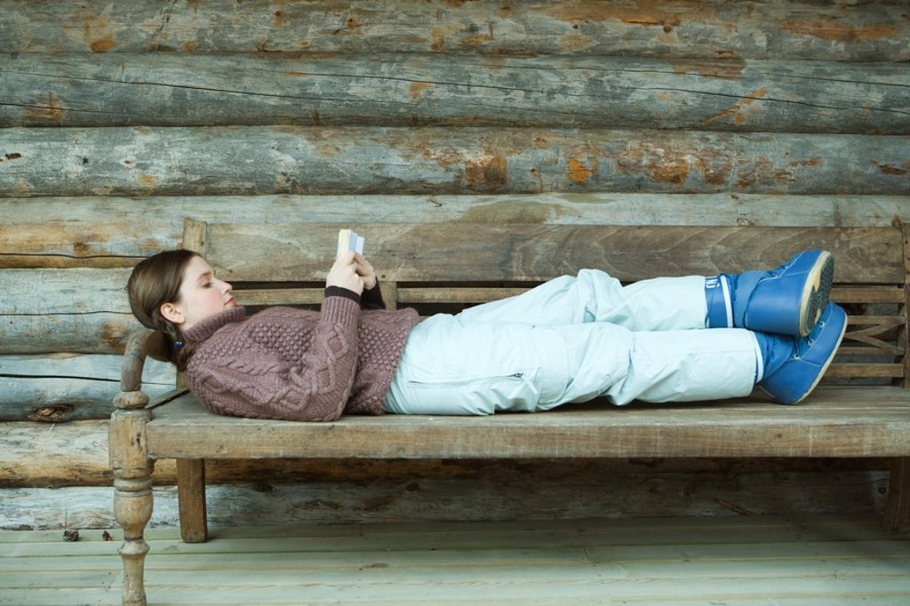 Teenage girl lying on back, reading book, wearing winter clothing : Stock Photo
