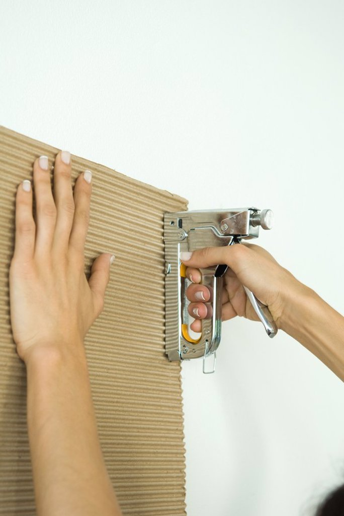 Woman stapling corrugated cardboard, cropped view of hands : Stock Photo