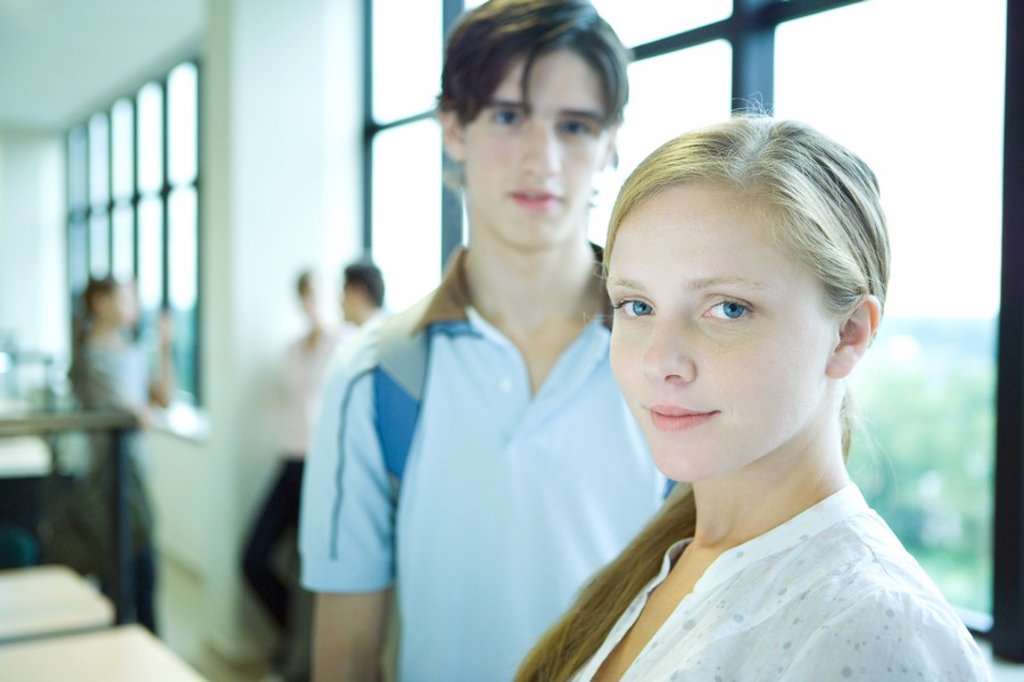 Stock Photo: 1569R-9027039 Female student smiling at camera, sideways glance, male peer in background