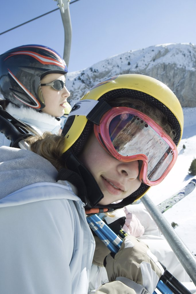 Two young skiers on chair lift, one smiling at camera : Stock Photo