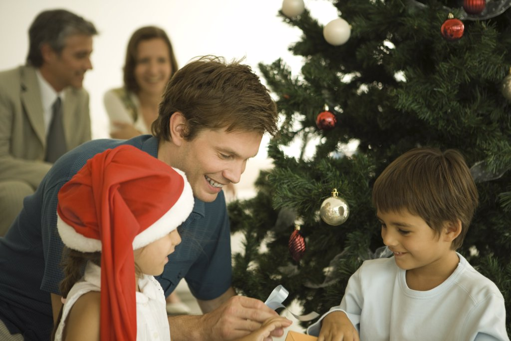 Stock Photo: 1569R-9027152 Father and two children sitting by Christmas tree, opening presents together, daughter wearing Santa hat