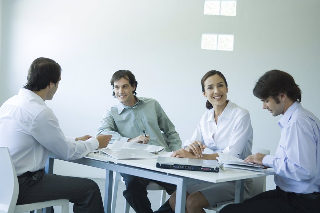 Business associates seated at table, chatting, one smiling at camera : Stock Photo