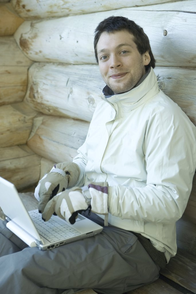 Stock Photo: 1569R-9027314 Man using laptop with gloves on, smiling at camera