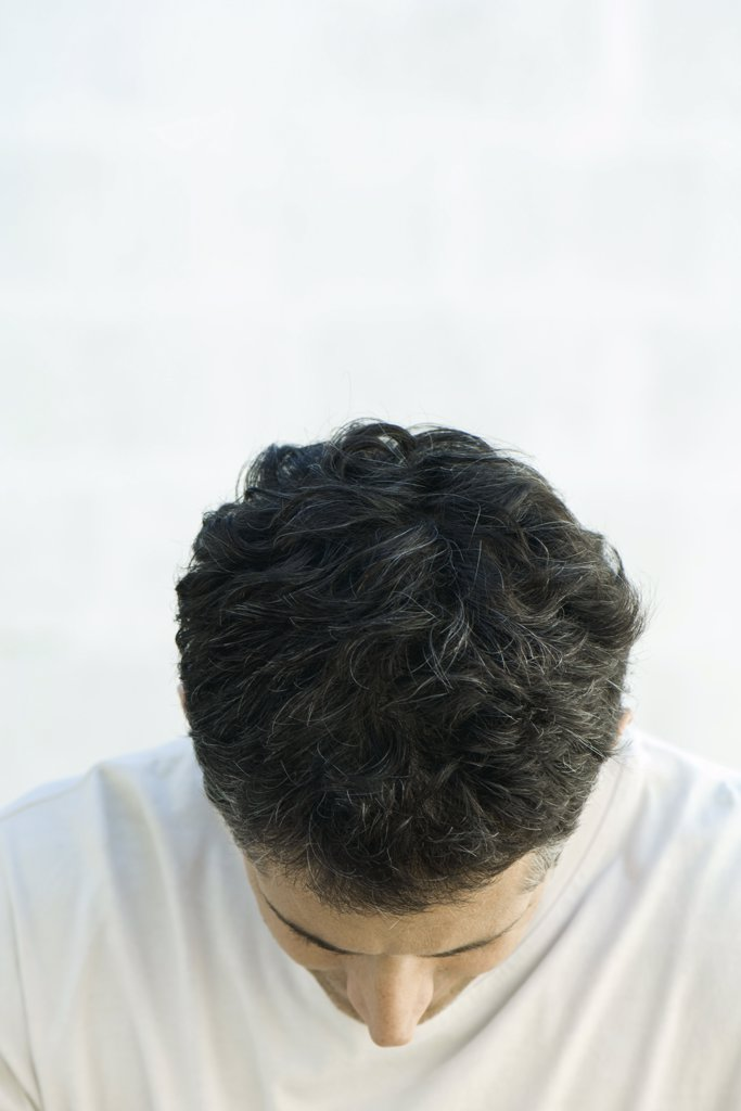 Mature man with head down, close-up : Stock Photo